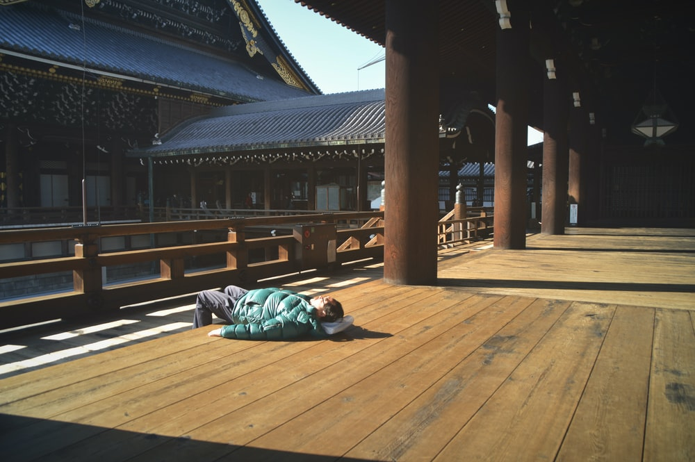 man lying on wooden floor near pillars and building
