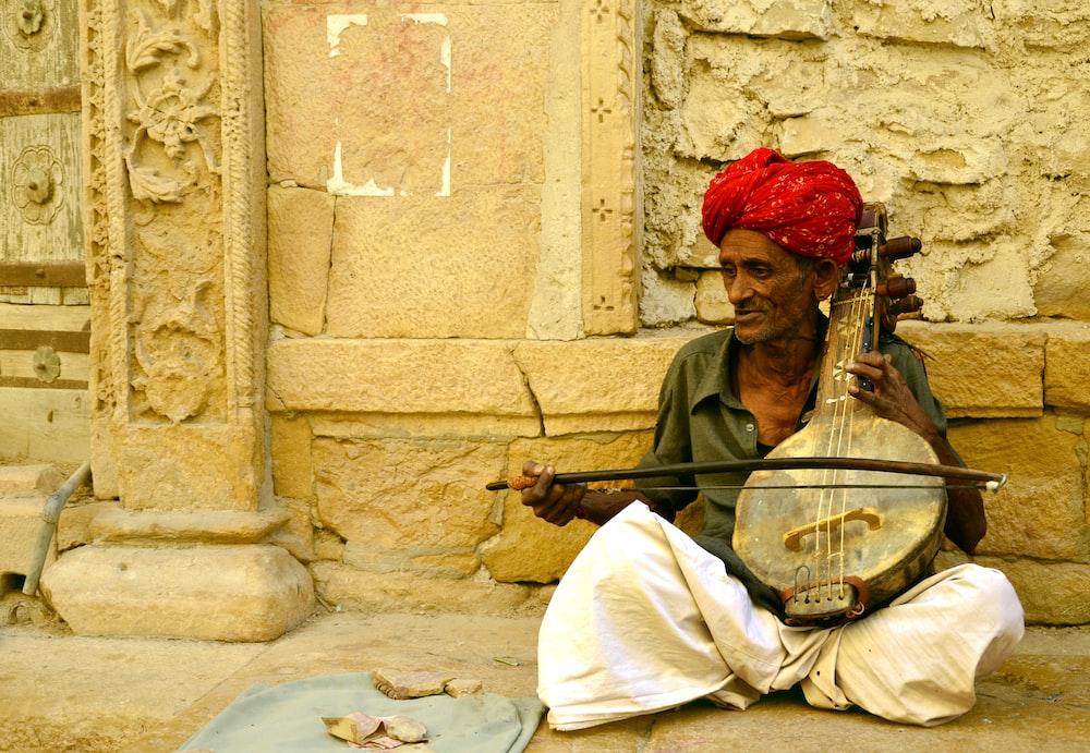 man wearing red hijab headdress playing music instrument