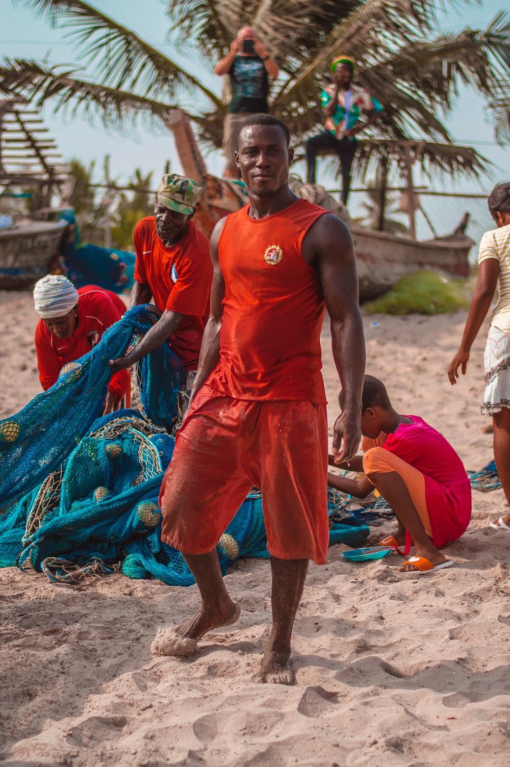 man wearing orange tank top standing near green coconut tree