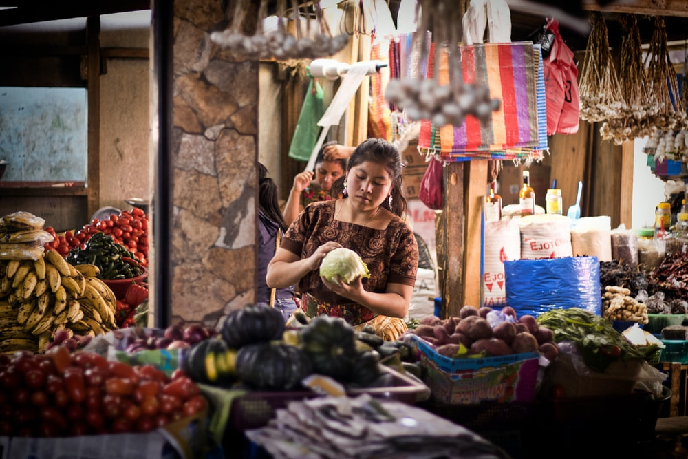 woman sitting near vegetable stand