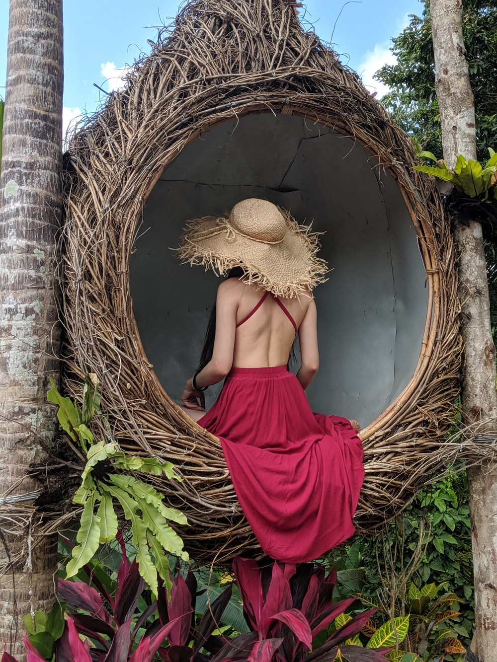 woman wearing pink backless dress sitting on wicker hanging chair