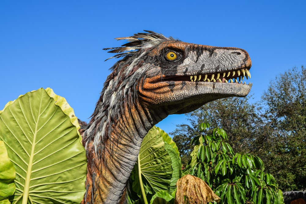 gray and brown dinosaur surrounded by trees during daytime