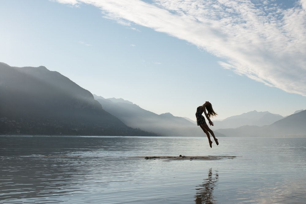 silhouette of jumping woman on raft in middle of lake
