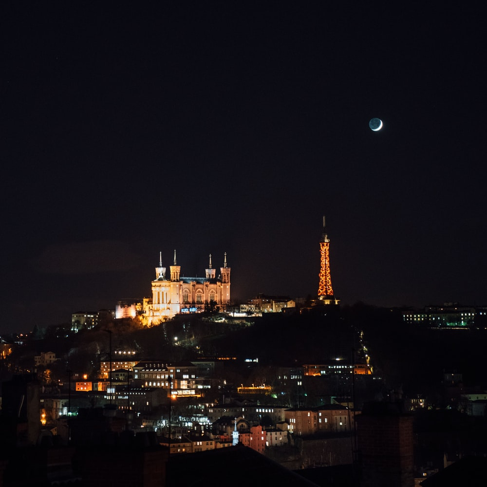 crescent moon over lighted city skyline
