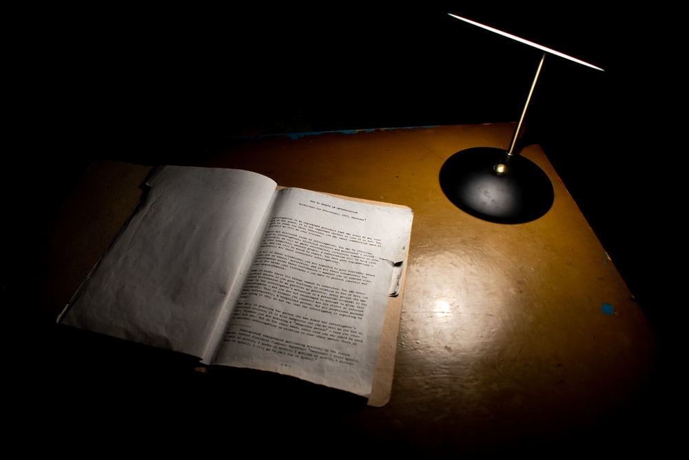 open book beside black table lamp