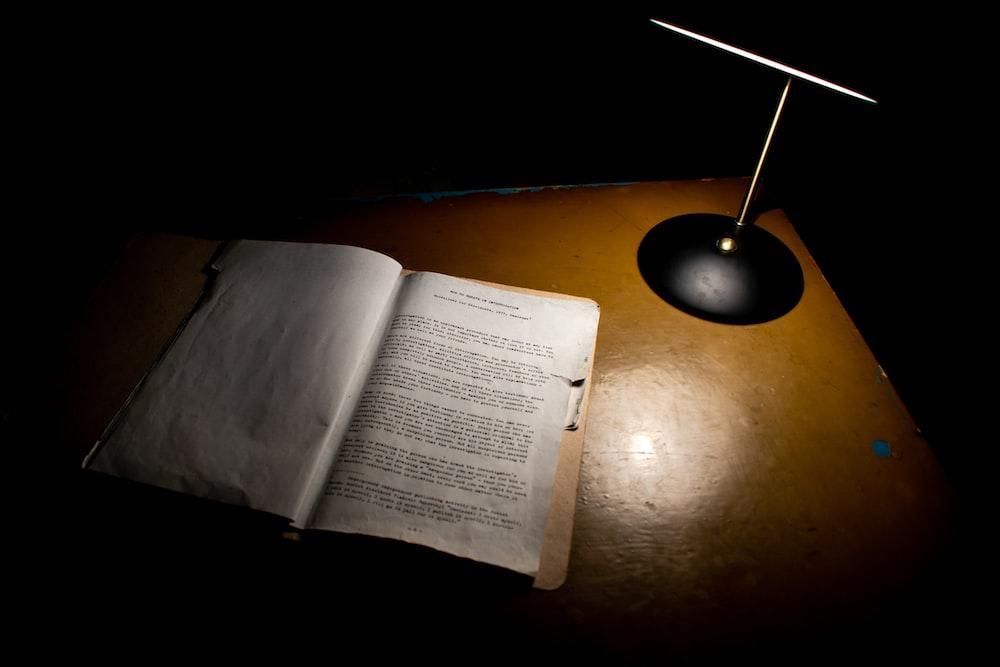 open book beside black table lamp
