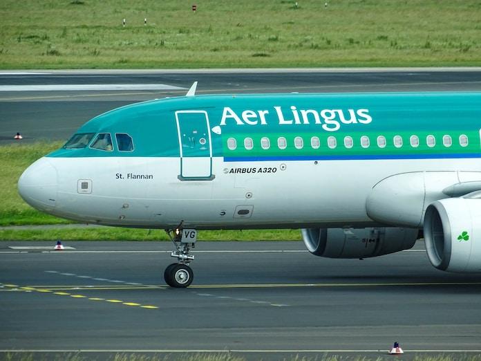 green and white Aer Lingus plane landing on railway