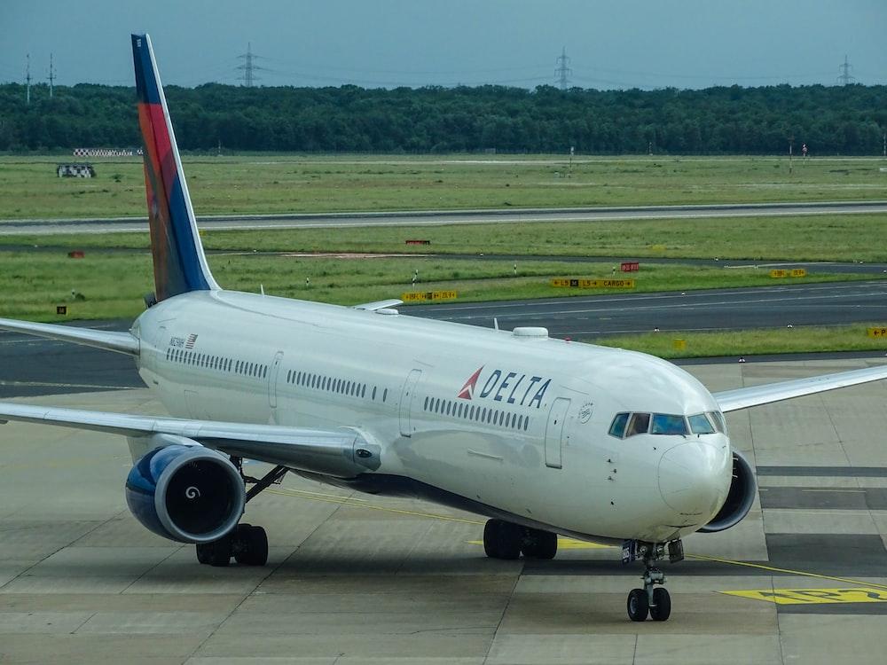 white Delta airplane on airport