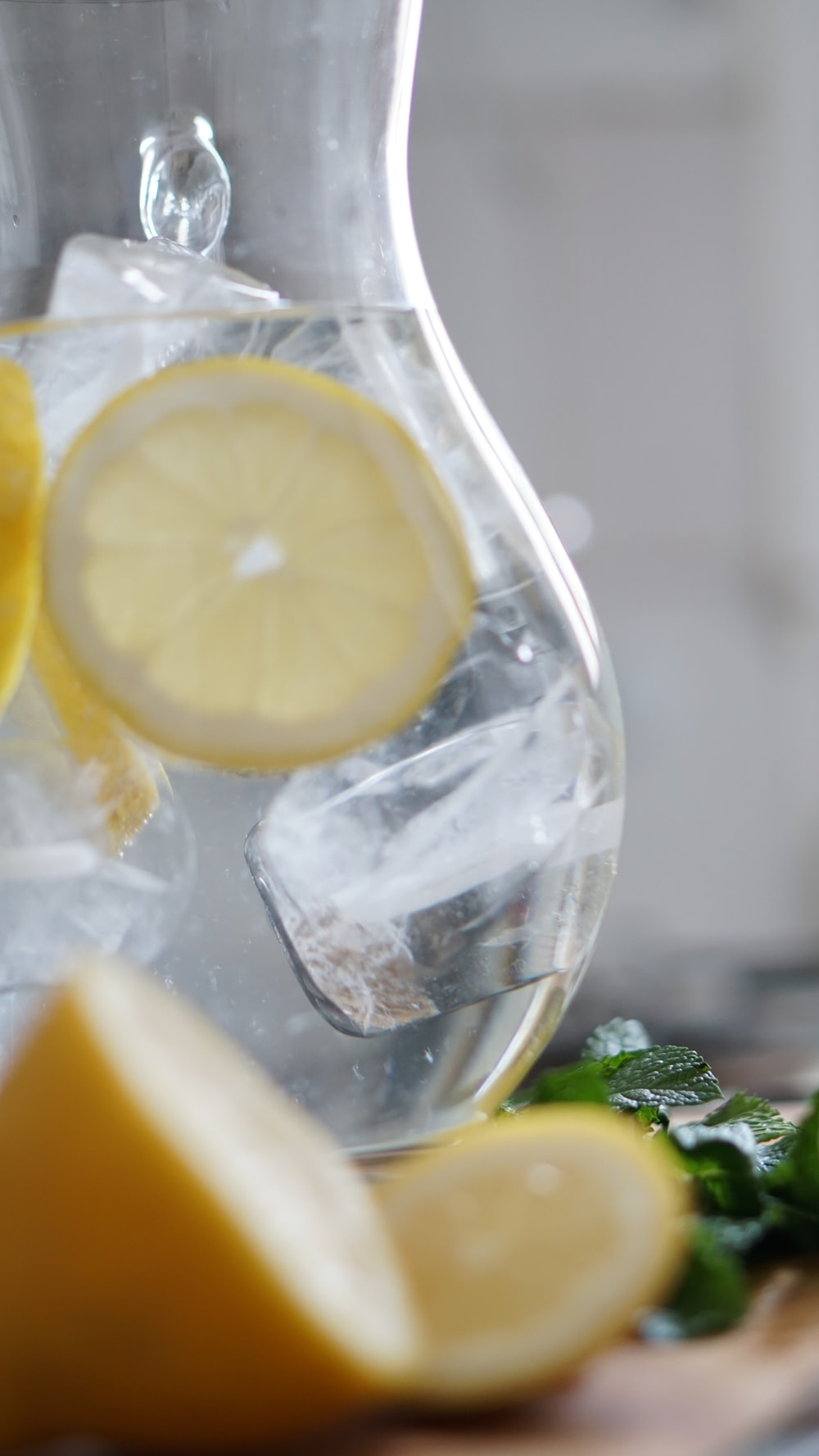 sliced lemon inside pitcher with ice cubes
