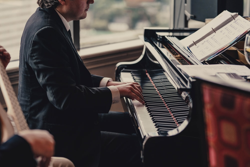 selective focus photography of person playing piano