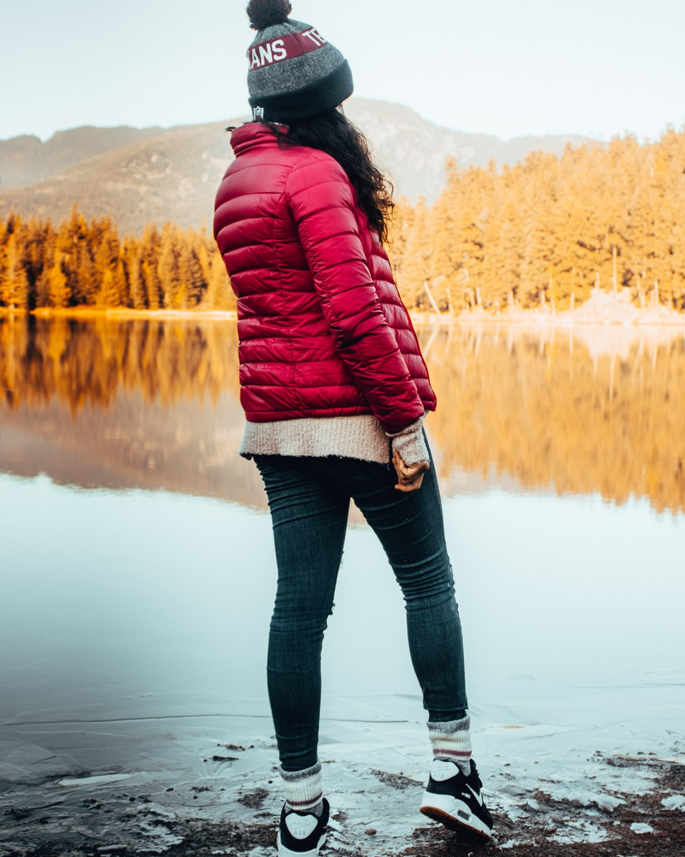 woman in red bubble jacket and blue skinny denim jeans standing in bank of lake