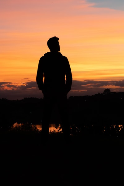silhouette of man under yellow sky