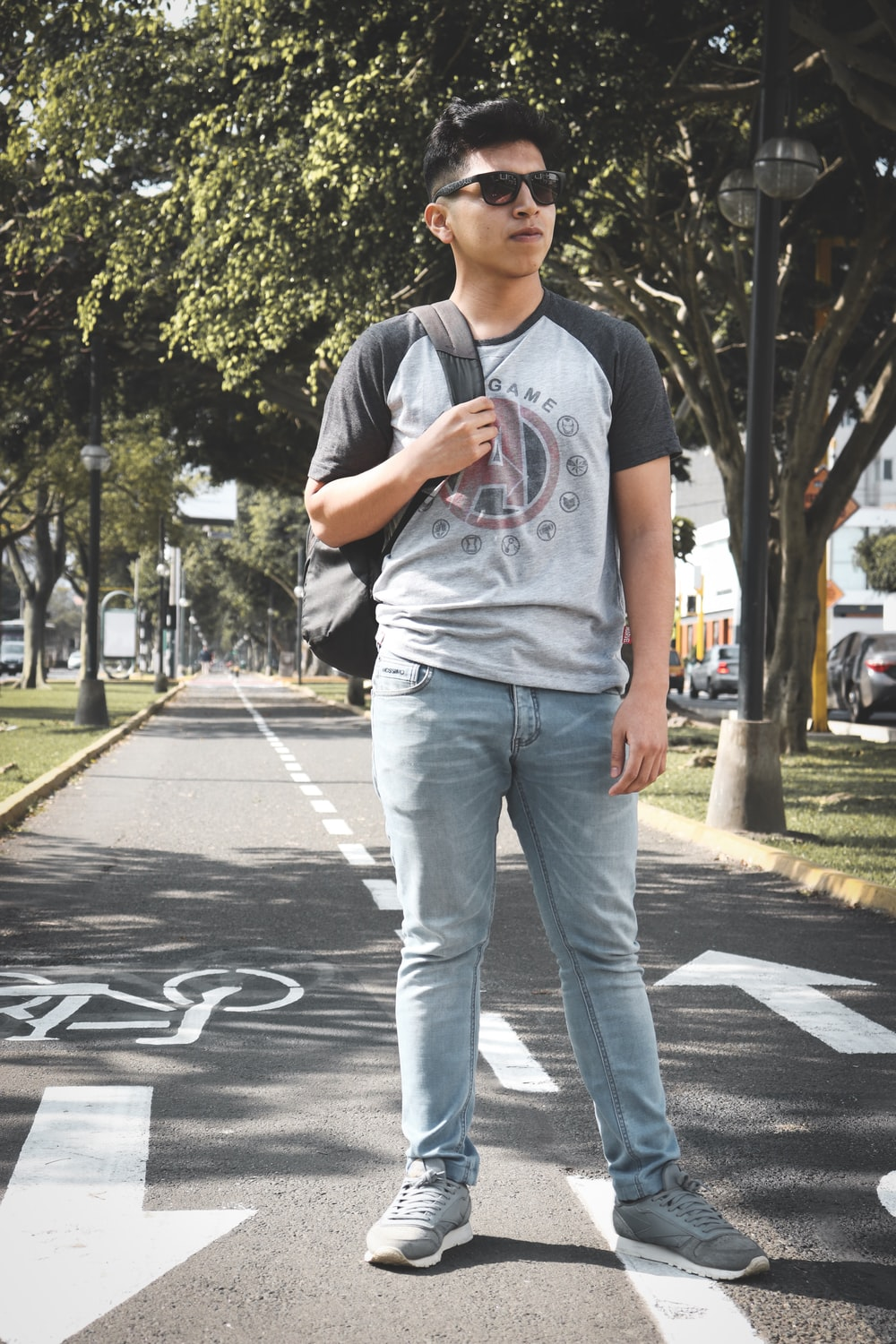 man standing on concrete road near trees