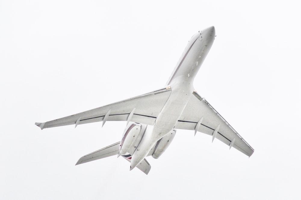 white passenger plane passing overhead