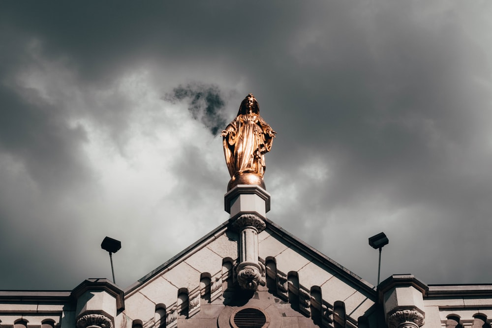 brown man in robe statue on top of building