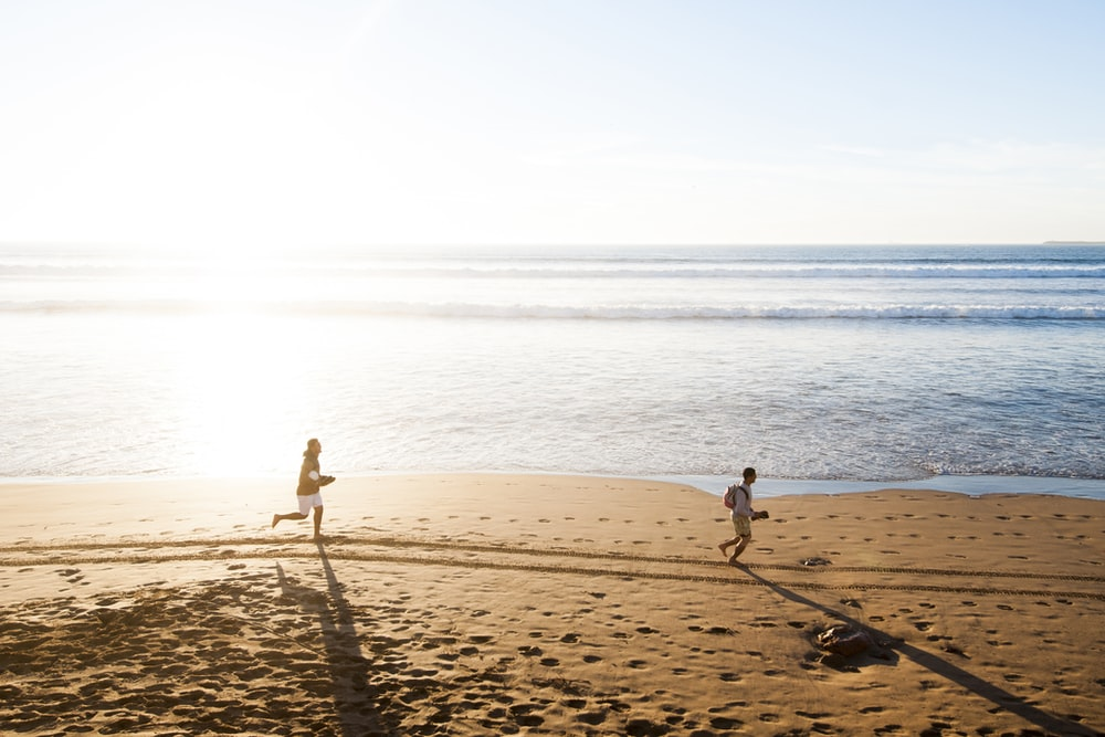 man chasing child in beach