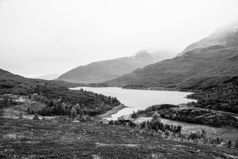 grayscale photo of lake between hills