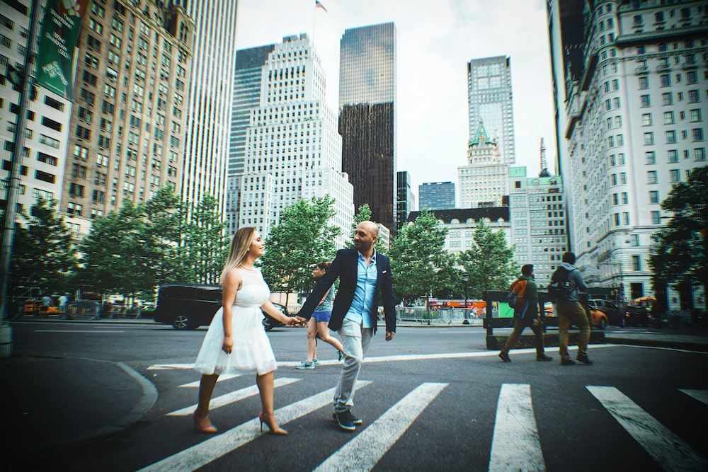 man and woman crossing street hand in hand