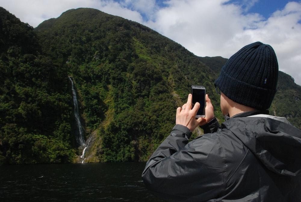 man in black jacket taking photo of waterfalls
