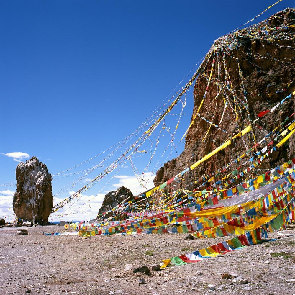 flaglets hanging on rock formation during daytime
