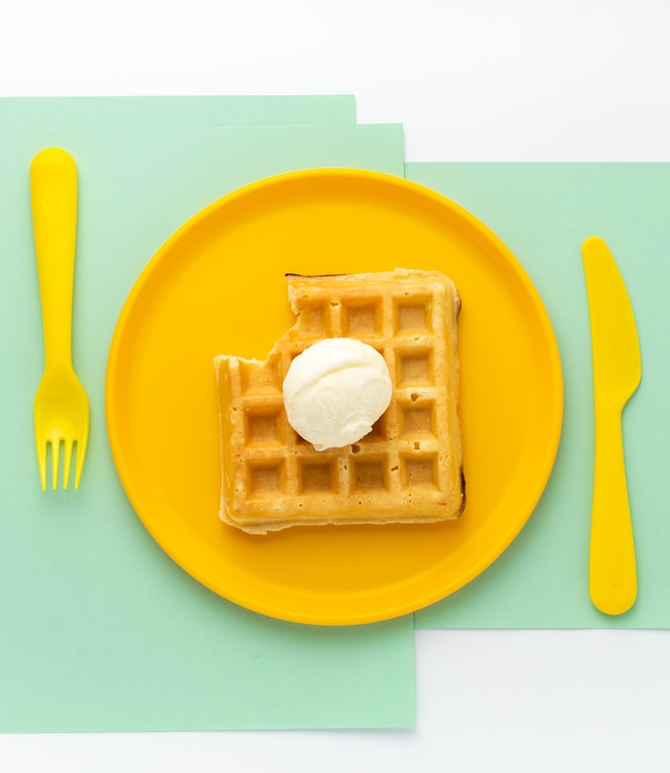 A flat-lay picture of a waffle on a yellow plate, with a fork and knife on either side of the plate and a teal background.