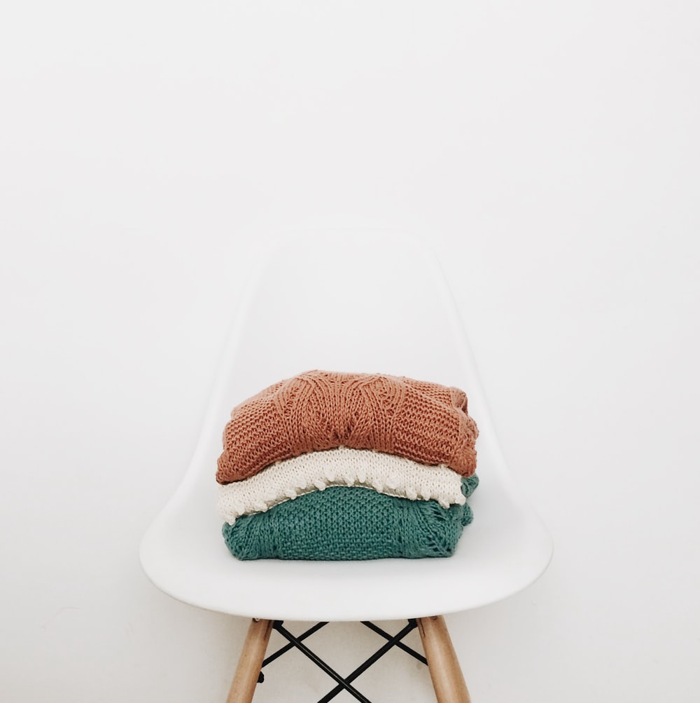 three knit piles of clothes on white chair