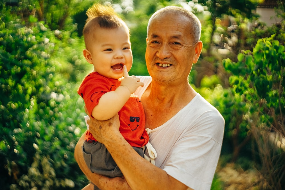 smiling man standing and carrying baby near green plants
