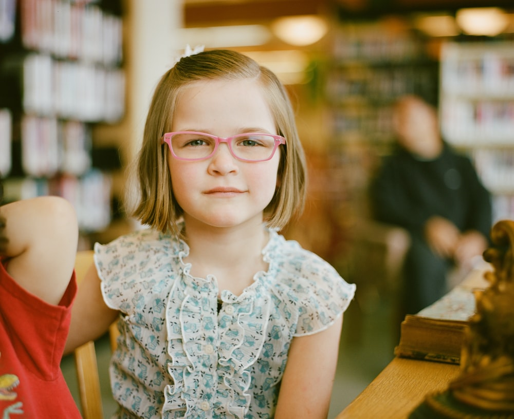 selective focus of girl sitting at table