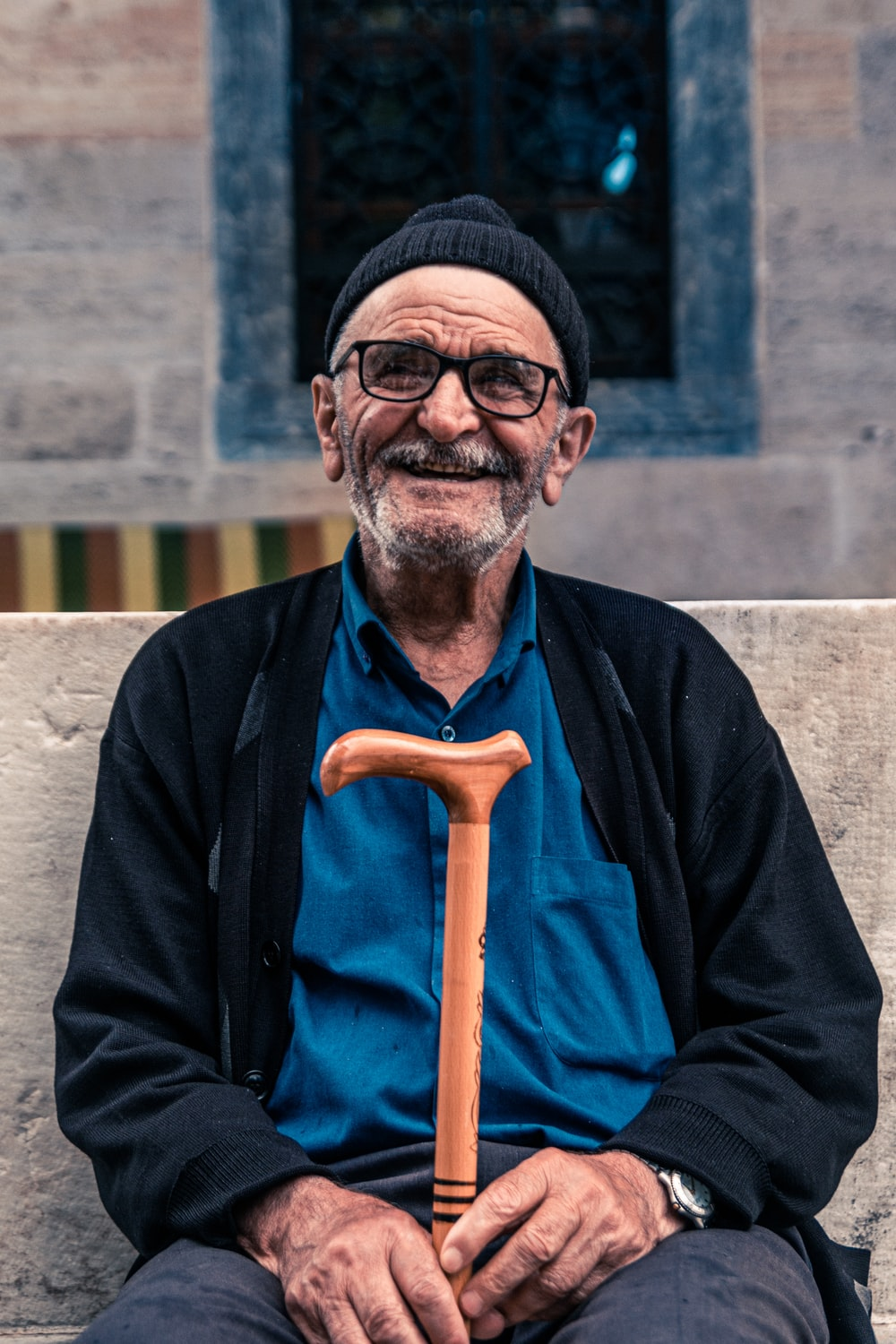 smiling man seated on bench holding cane