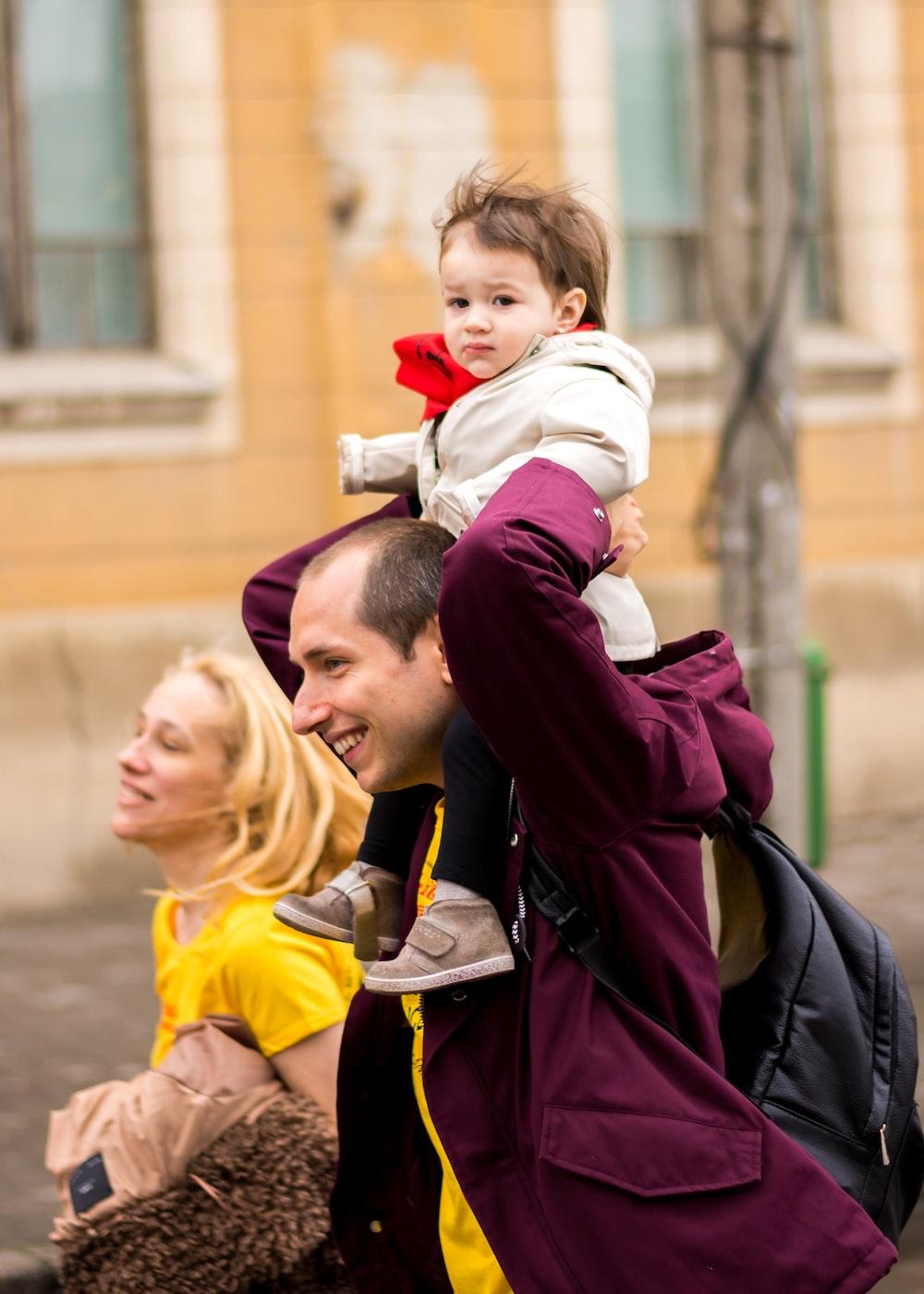 smiling man carrying toddler beside smiling woman