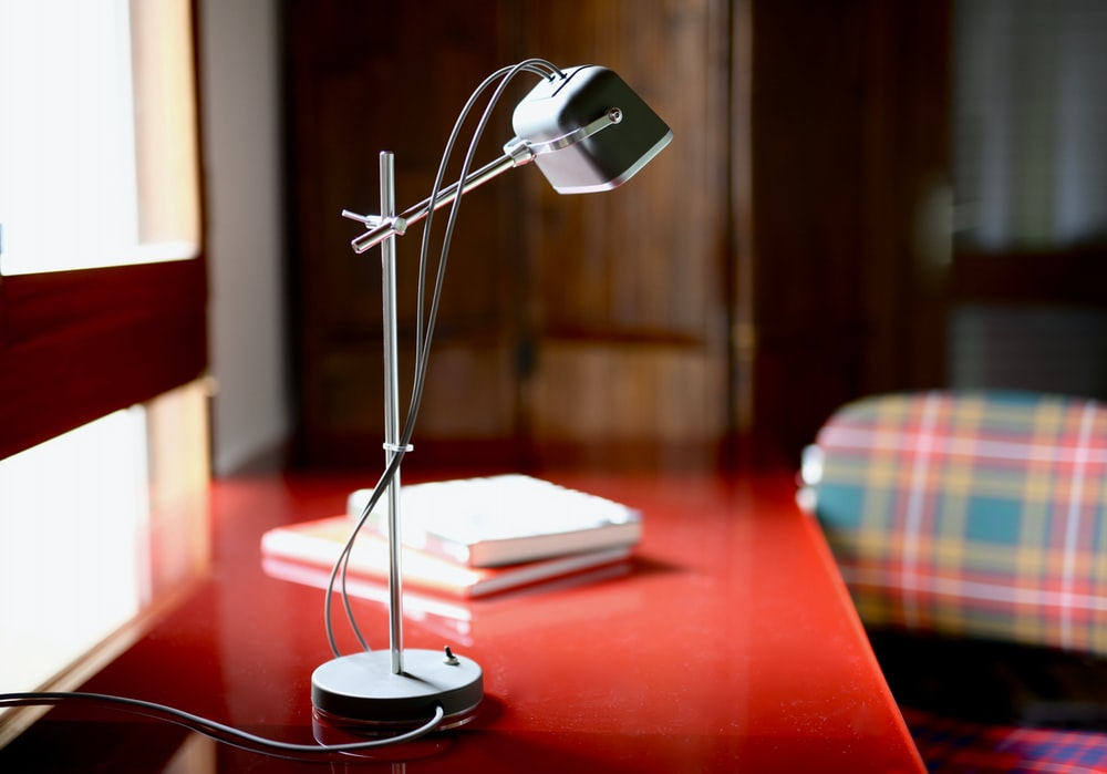selective focus photo of gray and white articulated table lamp