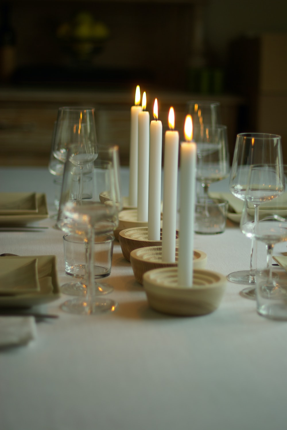 lighted five white candles on table with wine glasses