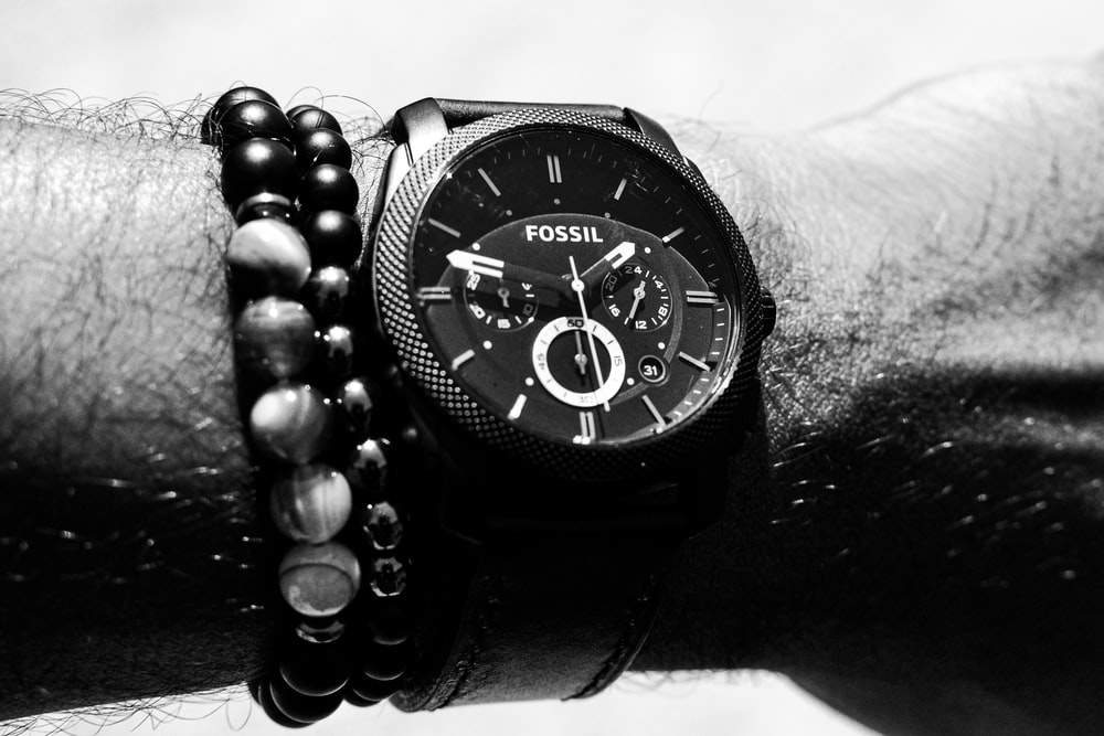 person wearing round Fossil chronograph watch with link band displaying 01:47 time