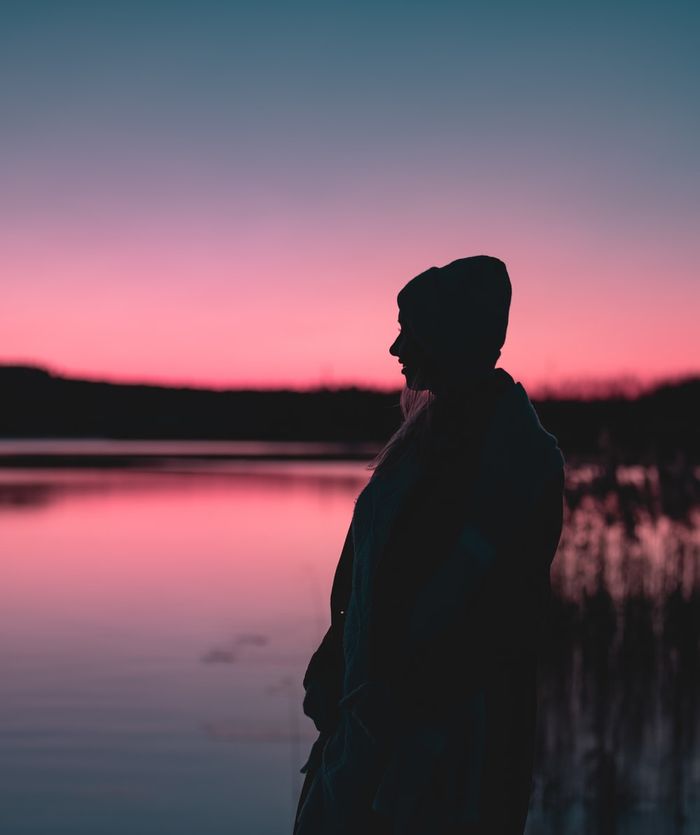 silhouette photography of person standing near body of water