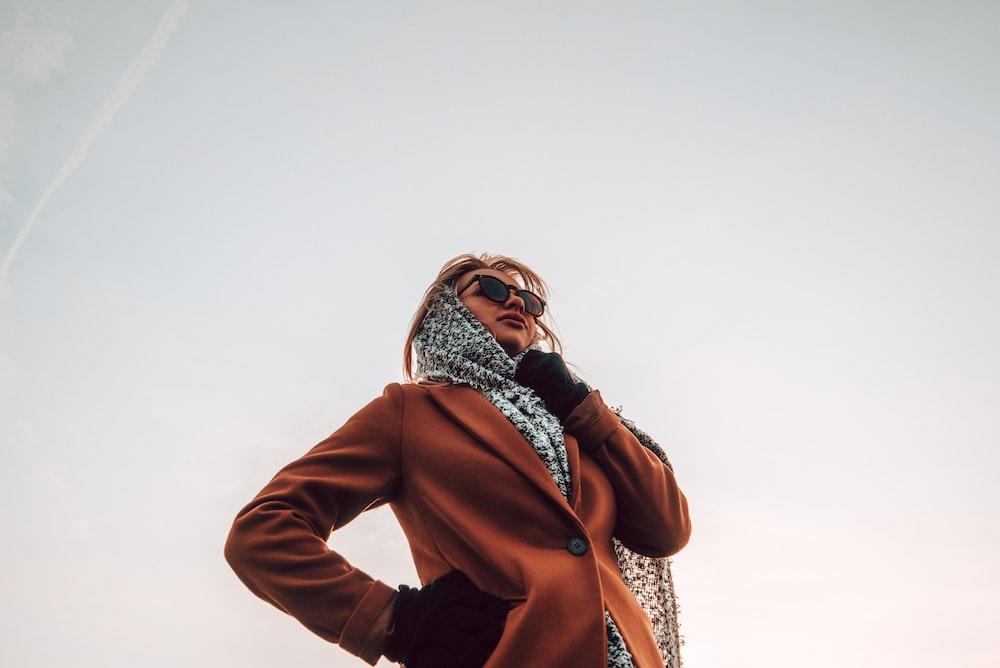 woman wearing brown peaked-lapel topcoat