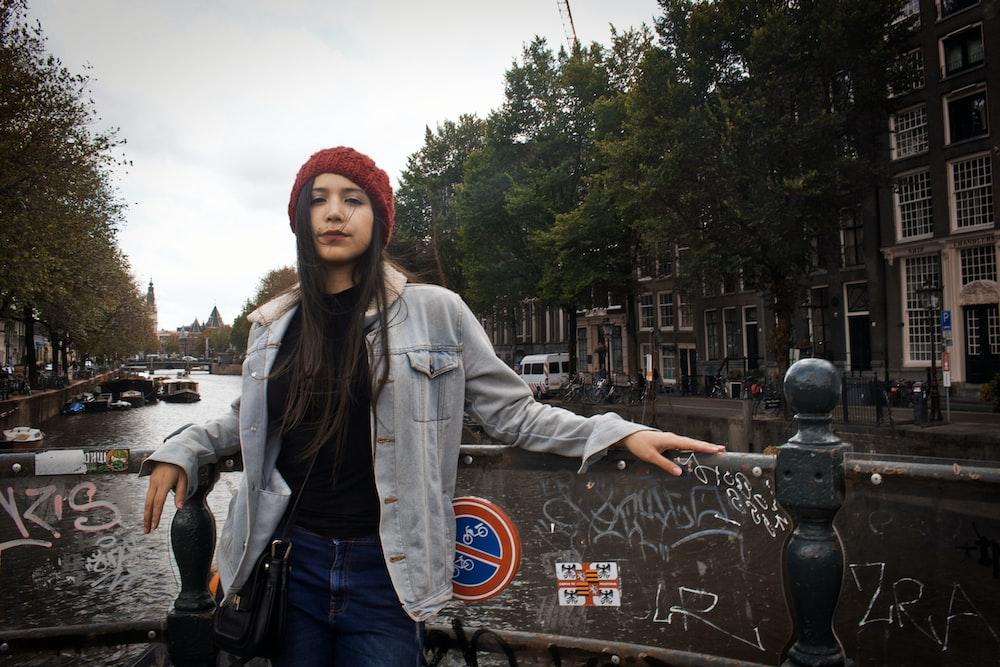 灰色の柵の横に立っている女性