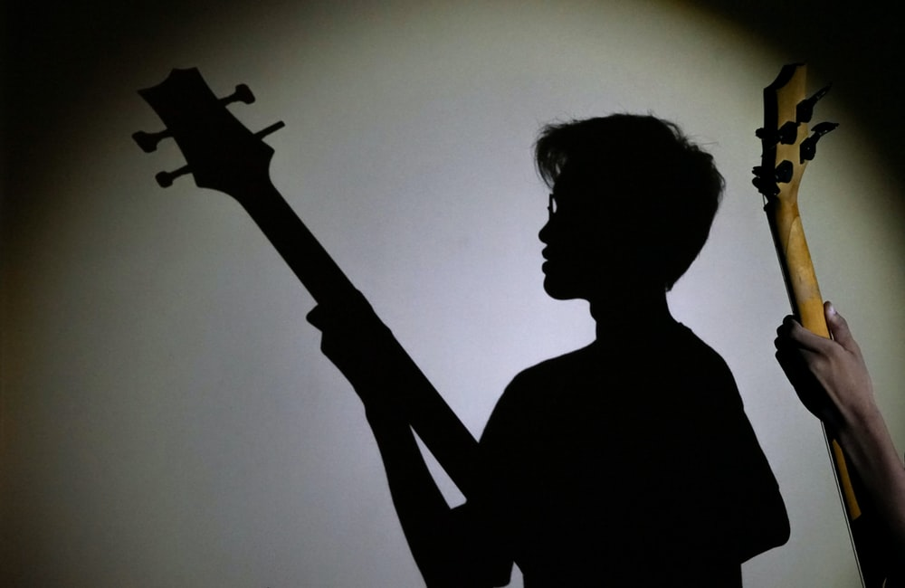 person playing guitar showing shadow