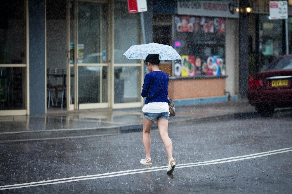 woman crossing on street holding umbrella