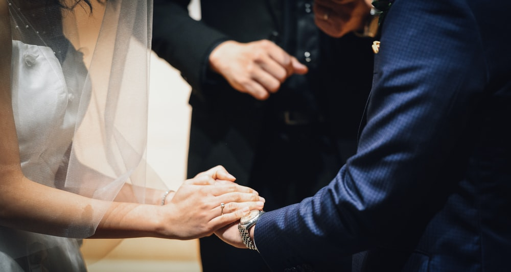 woman holding man's hand during wedding ceremony