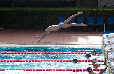 man dive on swimming pool during daytime diving teams background