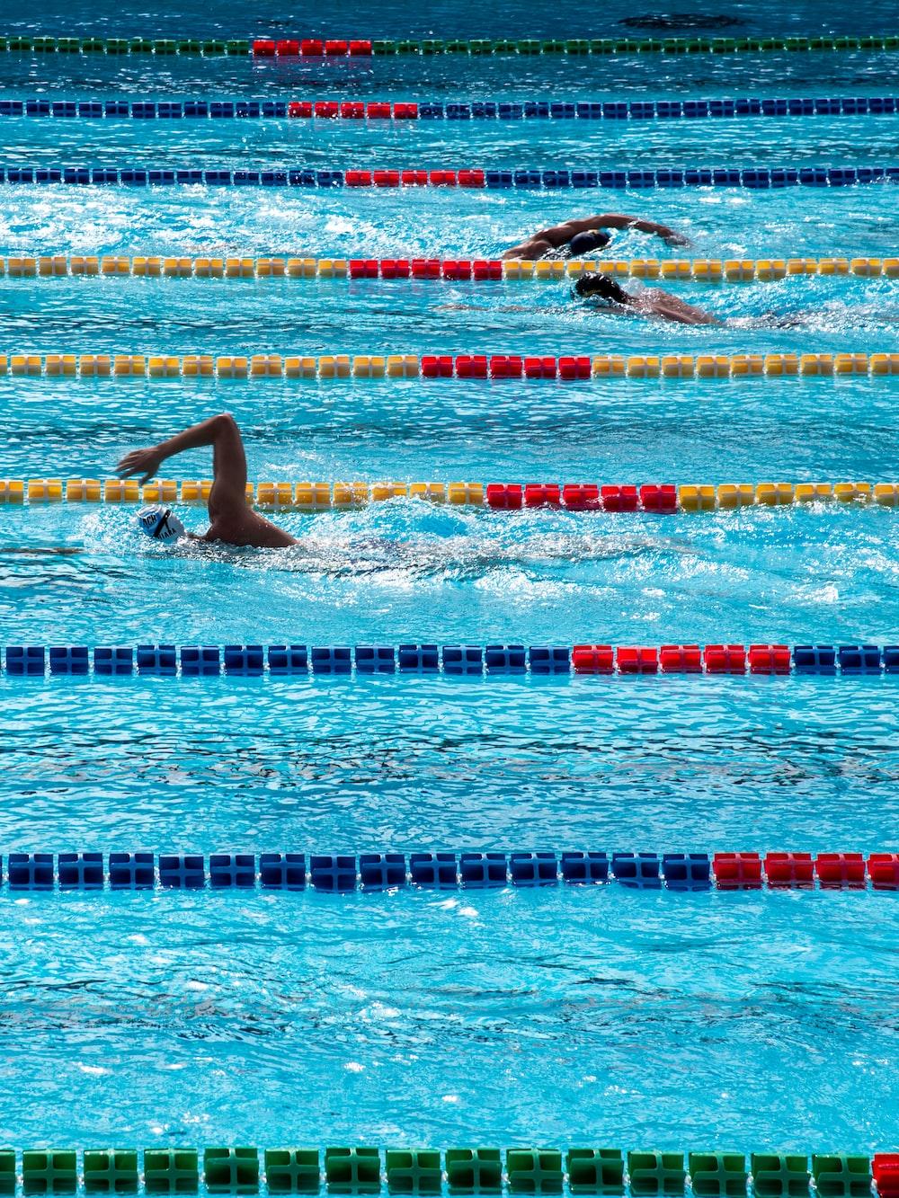 three person swimming on pool