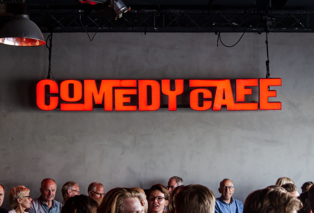 people gathering inside Comedy Cafe building