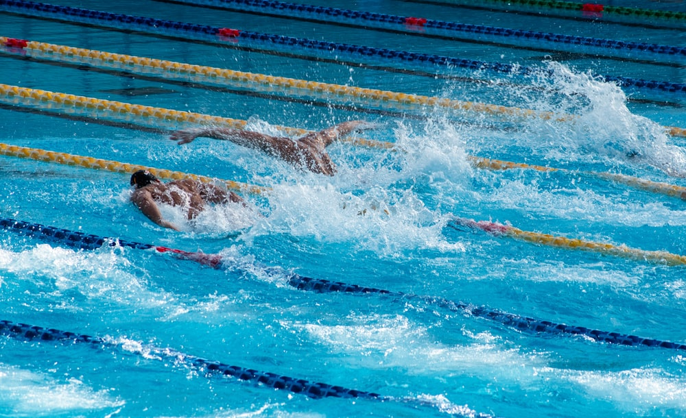 two men swimming doing butterfly strokes