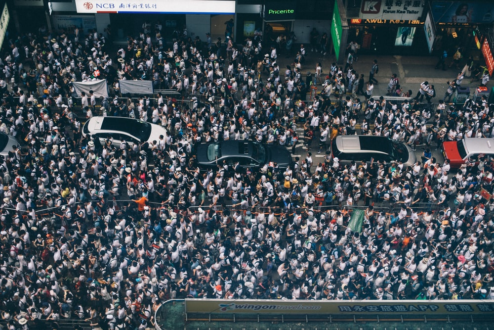 aerial photography of four cars surrounded with people
