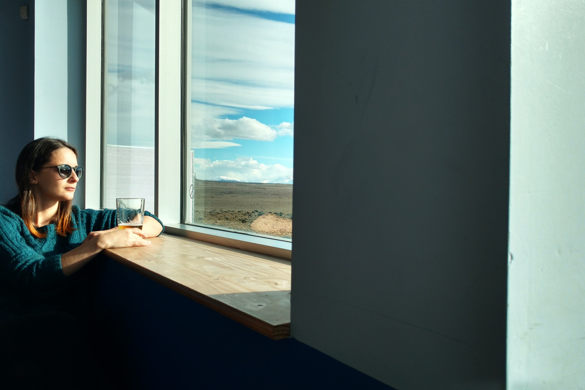 woman sitting beside window while looking outside
