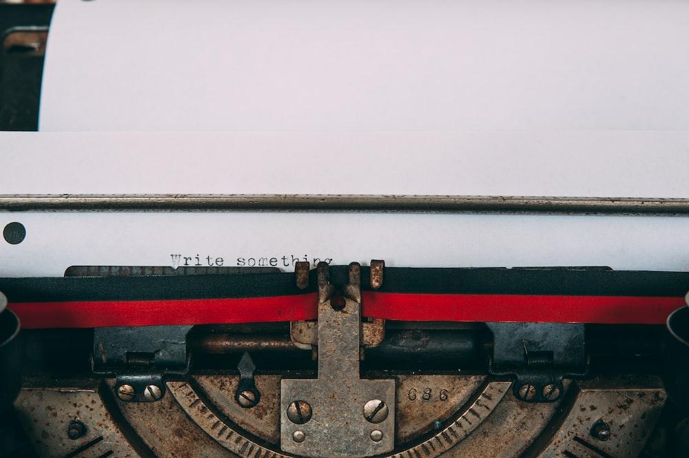 typewriter with paper displaying write something text