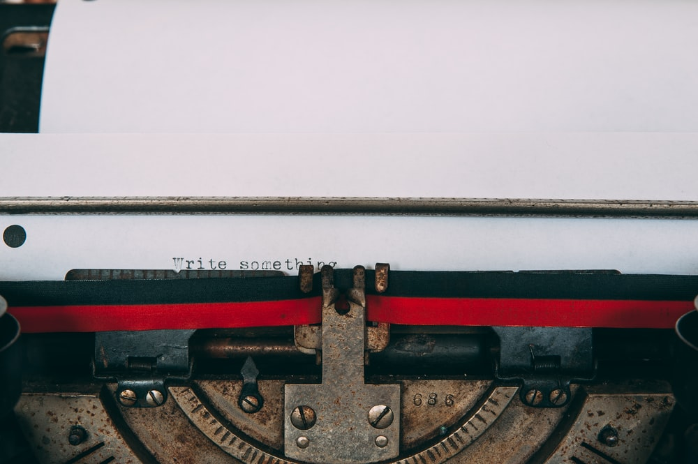typewriter with paper displaying write something text