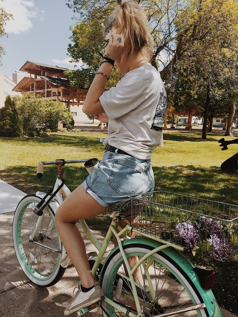 man riding white and green cruiser bike