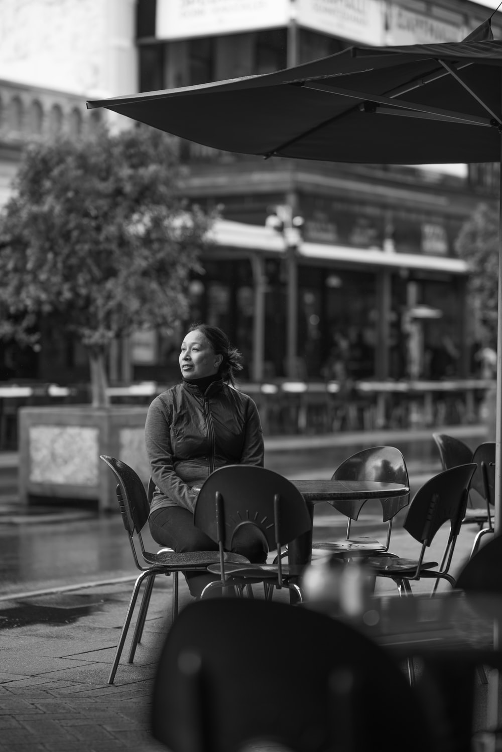 grayscale photo of woman sitting on chair