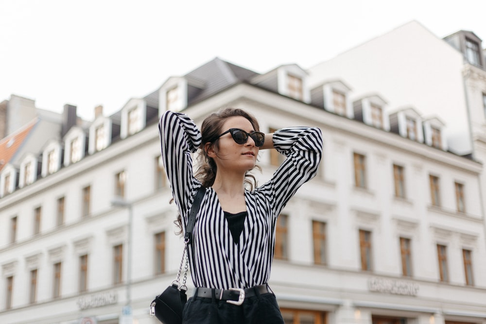 woman with both hands behind her head in front of building during day
